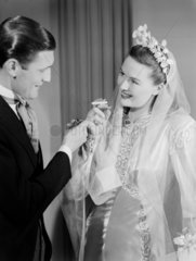 Groom lighting his bride's cigarette  c 1949.