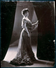 Woman in evening gown holding open a curtain  c 1900.