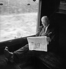 Man with his feet up reading a newspaper during a train journey  1950.