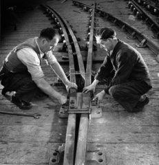 Two men assemble railway track in factory   Darlington Railway Company.