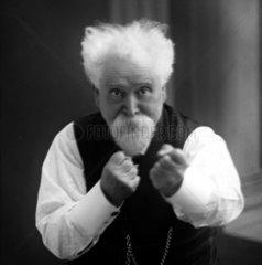 Sir Hiram Maxim with his fists raised  c 1900.