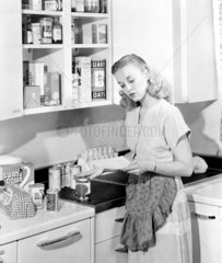 Woman putting food in a cupboard  1950.
