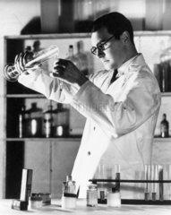 Laboratory technician pouring liquid into a test tube  c 1940s.