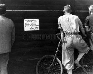 Men watching a motor race through a gap in a fence  Berlin  1930s.