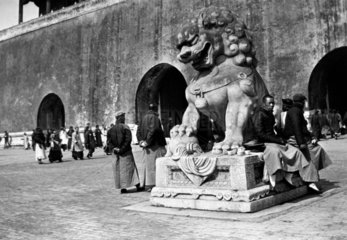 Crowd gathered by a statue of a lion outsid