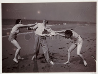 Man and two women play-fight on a beach  c 1930.