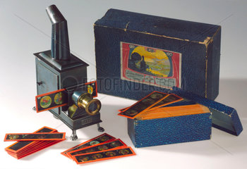 Child's magic lantern with twelve slides and original box  1913-1920.