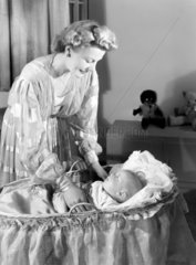 Woman with a baby in a cot  c 1949.