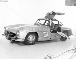 Model reclining in Mercedes wing-door car  c 1961.