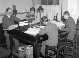 Four clerks at work in an office  October 1