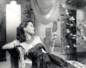 Glamorous young woman reclining on a couch  c 1945.