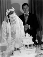 Bride  groom and wedding cake  c 1949.