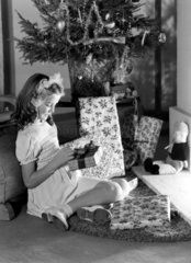 Little girl looking at Christmas presents  c 1950.
