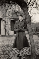 Woman standing beside a tree  1940s.