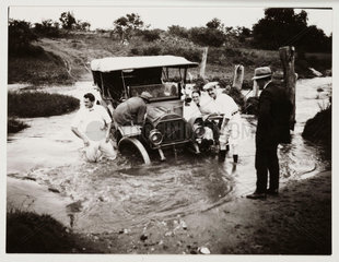 Car stuck in a ford  c 1910.