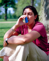 Young woman using an asthma inhaler  May 2000.