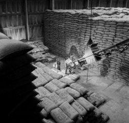 Workers in huge storeroom place bags of raw asbestos material on to belt.