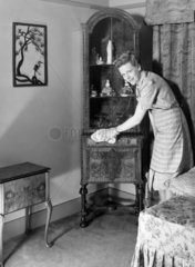 Woman polishing a cabinet  c 1950.