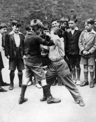 Boys fighting in the school playground  c 1930s.