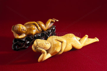 Netsuke showing reclining female figures.