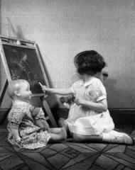 Girl drawing on a blackboard  c 1930s.