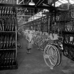 Female worker with overhead loading belt before assembly  British Cycle Co.