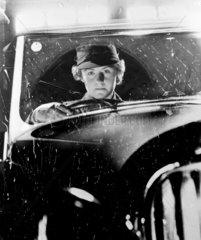 Woman driving a car in the rain  c 1950.