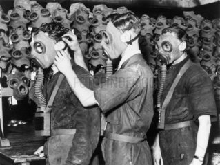 Three men wearing gas masks  c 1930s.
