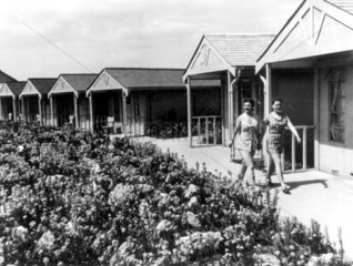 Two women walking past chalets at a Butlins holiday camp  8 July 1939.