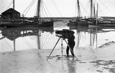 Photographer standing on an estuary mudflat taking a photograph  c 1900s.