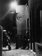 Men loitering in the street at night in a slum area of London  1937.