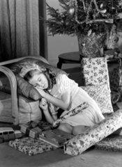 Little girl asleep under Christmas tree  c 1950.