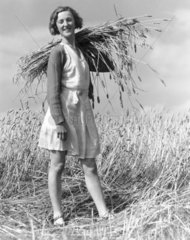 Land-girl with a sheaf of wheat over her shoulder  c 1930s.