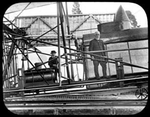 Maxim standing on the framing of his 1894 machine outside the hangar  1894.