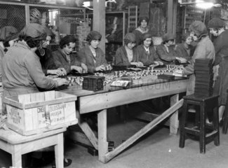 Women factory workers packing tins of 'Cher