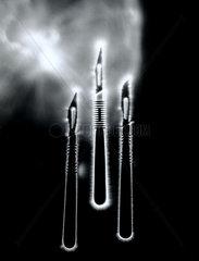 Kirlian photograph of three scalpels.