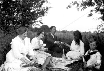 Family picnicking in the countryside  c 191