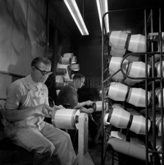 two men twisting fibre glass material in textile department  Glasgow  1967.