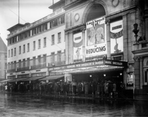 People queuing in the rain  Empire cinema  London  3 May 1931.