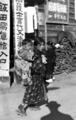 Young Japanese girl carrying baby on her ba