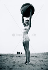 Young woman on tiptoes holding aloft a beach ball  c 1940s.