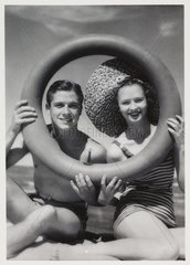 Man and woman looking through a rubber ring on beach  c 1935.