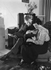 Couple relaxing at home with a cat  c 1930s.
