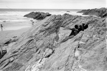 Two young couples canoodling on rocks  1967.