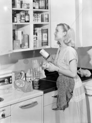 Woman putting tins in the kitchen cupboard  1952.