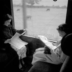 Women reading newspapers during their journey  1950.