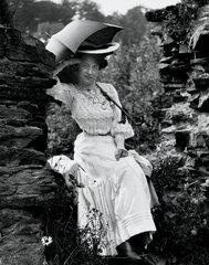 Edwardian woman sitting on a wall  c 1900s.