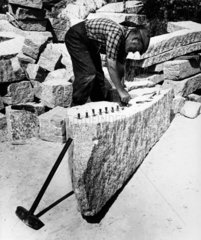 A mason inserting wedges in to De Lank granite block before splitting  1961.