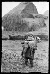 Little boy carrying a lamb  1932.