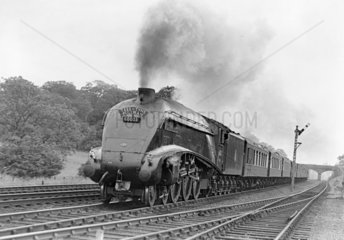 Steam locomotive with carriages  c 1940s.